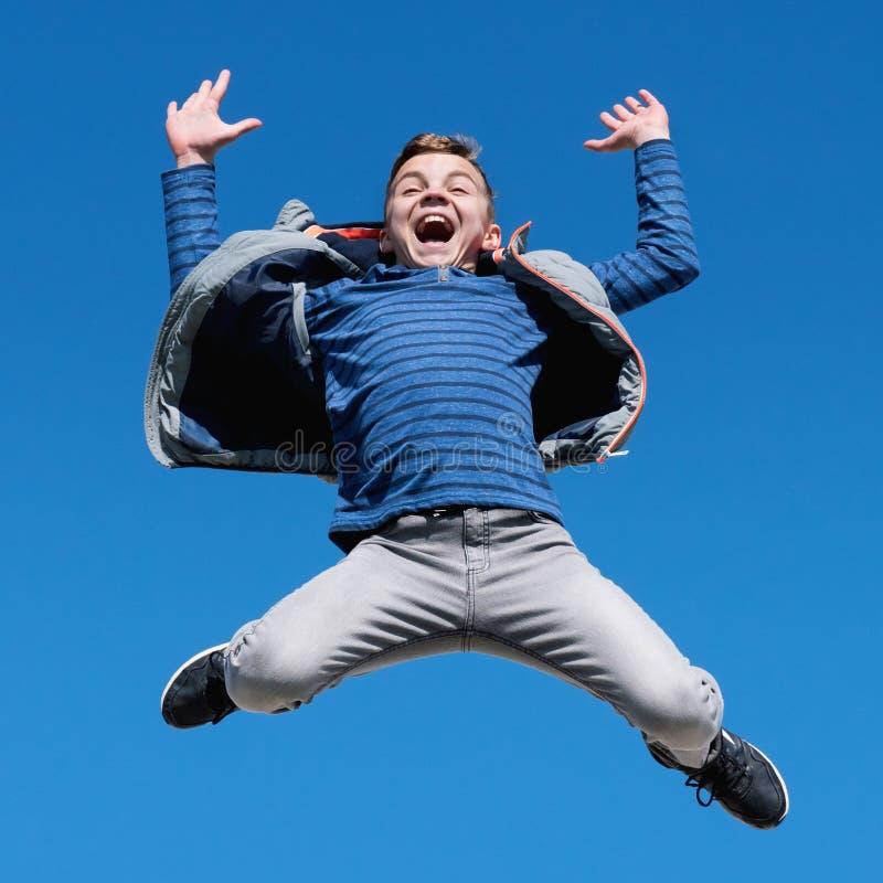 Lycklig tonårig pojkebanhoppning mot klar himmel royaltyfria foton