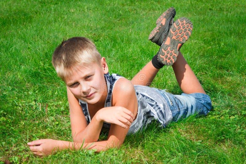 Lycklig tonåring som ligger på gräset royaltyfri foto