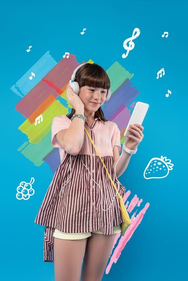 Lycklig tonåring som tycker om ljus sommar och lyssnar till musik royaltyfria foton