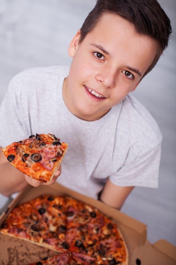 Lycklig tonåringpojke som har all en hel ask av pizza för honom royaltyfri bild