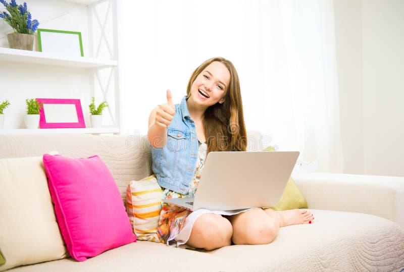 Lycklig tonårs- flicka för skönhet som använder hennes bärbar dator som sitter på soffan fotografering för bildbyråer