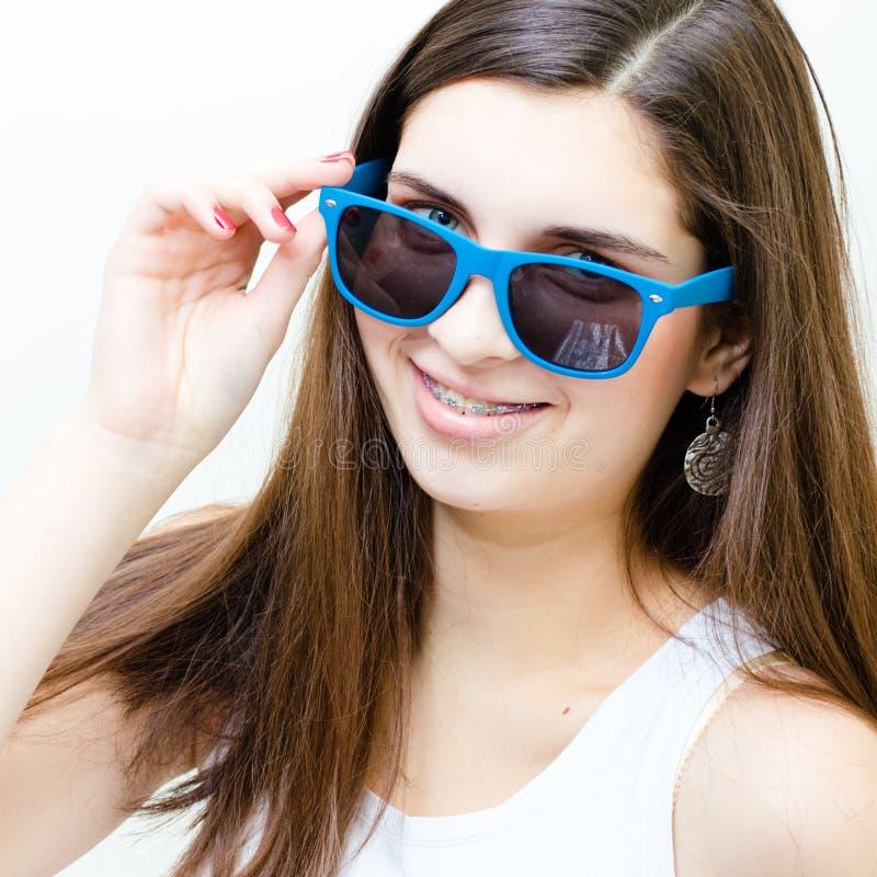 Lycklig tonårs- flicka i roligt le för solglasögon arkivfoto