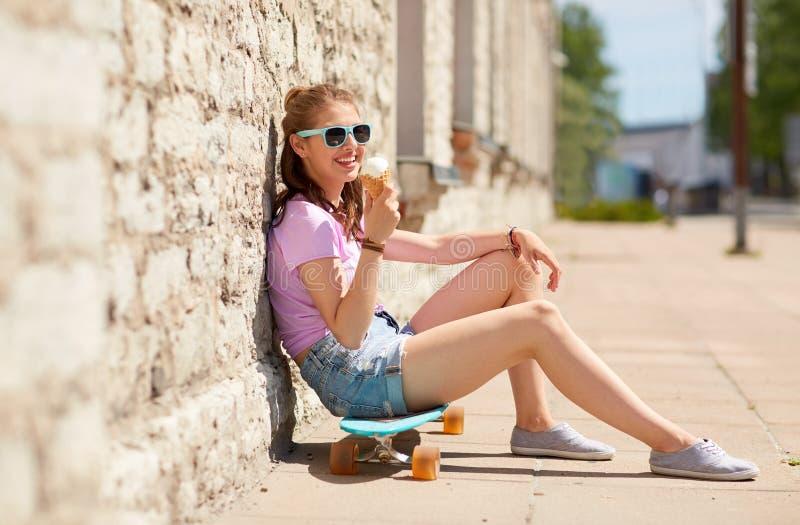 Lycklig tonårs- flicka med longboard som äter glass fotografering för bildbyråer