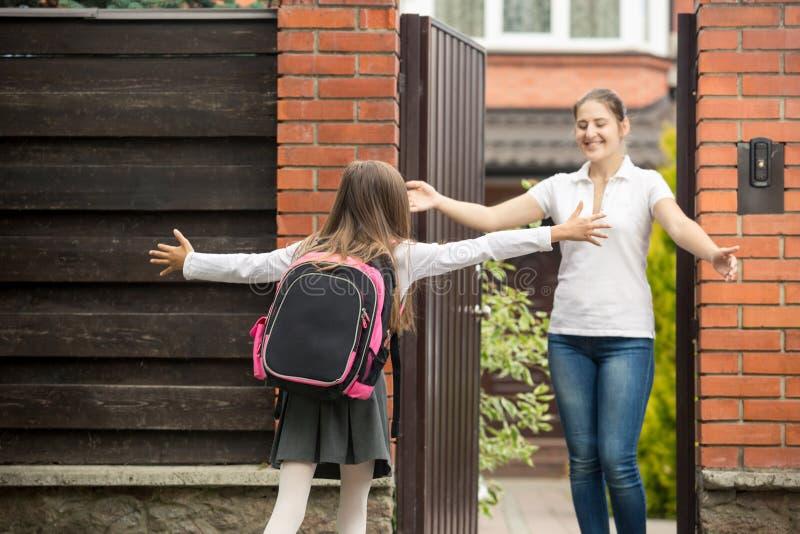 Lycklig tonårs- flicka som kör till hennes moder, når att ha gått från skola royaltyfri fotografi
