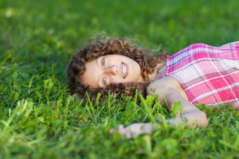 Lycklig tonårs- flicka som ligger på gräs royaltyfria foton