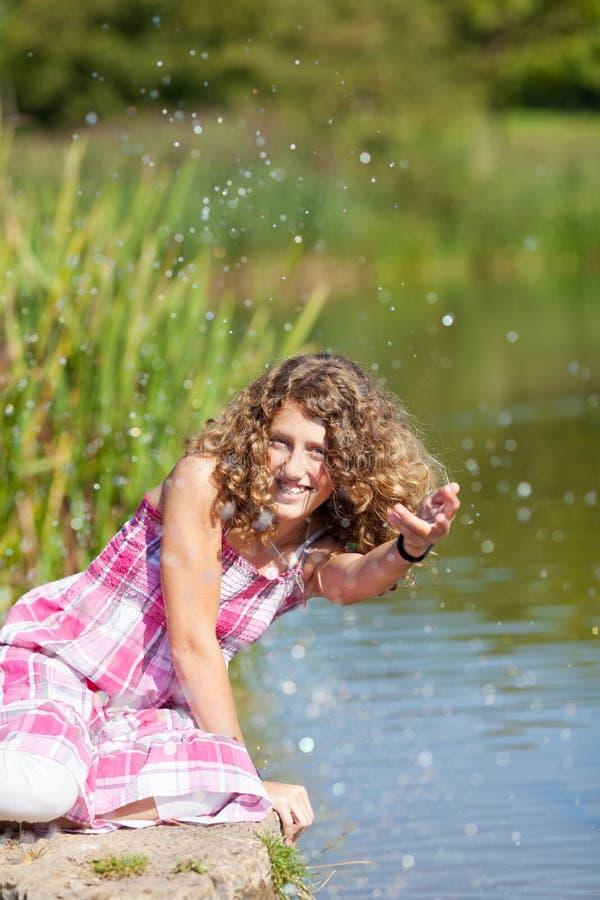 Lycklig tonårs- flicka som spelar med vatten arkivfoto