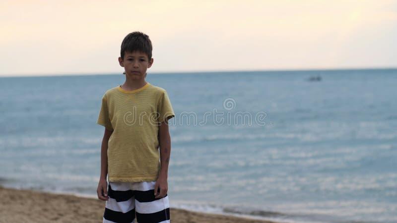 Lycklig tonårs- pojke på stranden som ser kameran i aftonen arkivfoton