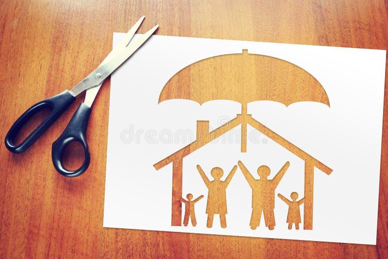 Lycklig traditionell familj i deras eget hus under skydd Begrepp av försäkring och säkerhet royaltyfri bild