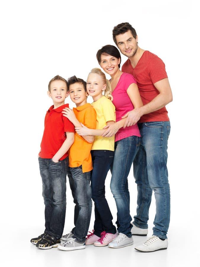 Lycklig trebarnsfamilj som tillsammans står arkivbild