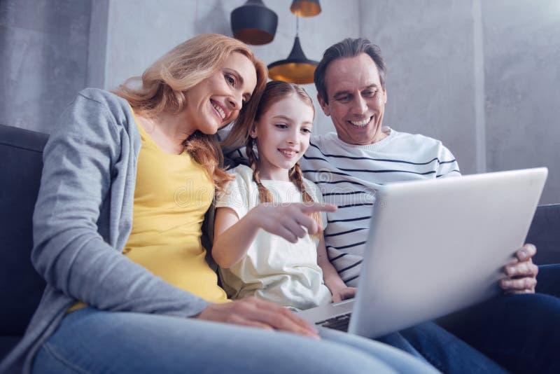 Lycklig trevlig flicka som pekar på bärbar datorskärmen fotografering för bildbyråer