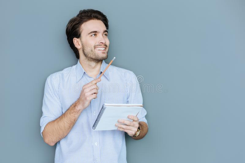 Lycklig trevlig man som rymmer hans anteckningsbok arkivbilder