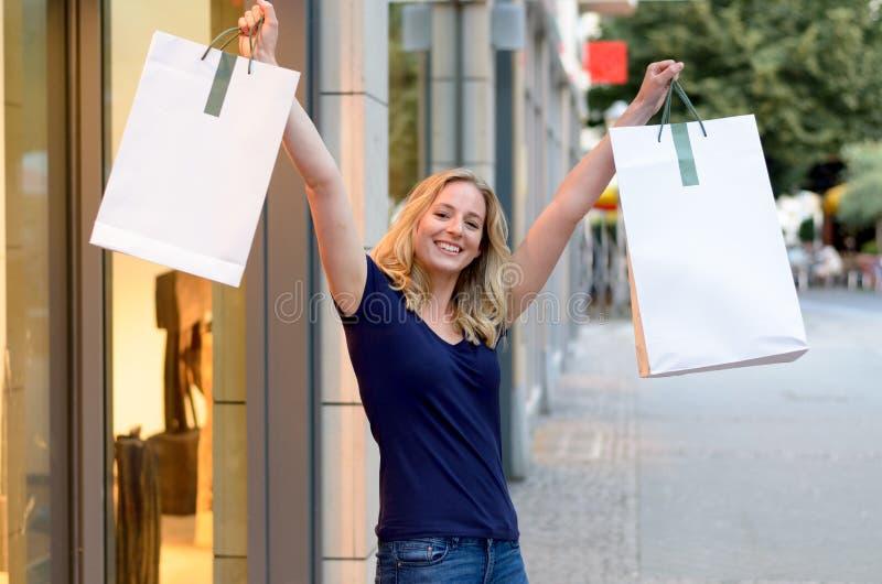 Lycklig triumferande shoppare för unga kvinnor royaltyfria bilder