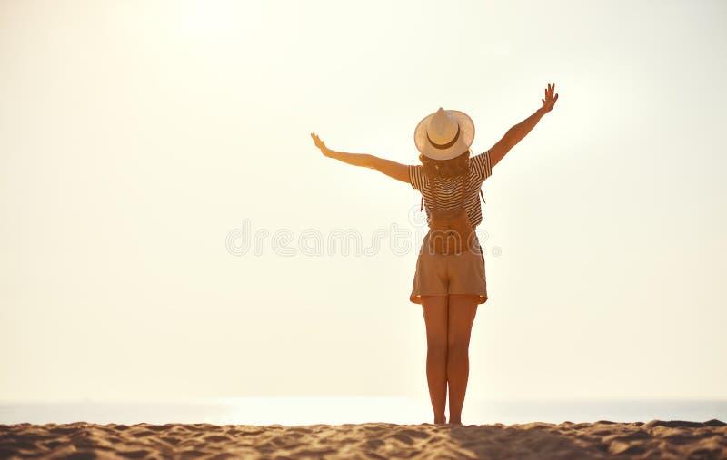 Lycklig turist- flicka med ryggs?cken och hatten p? havet fotografering för bildbyråer