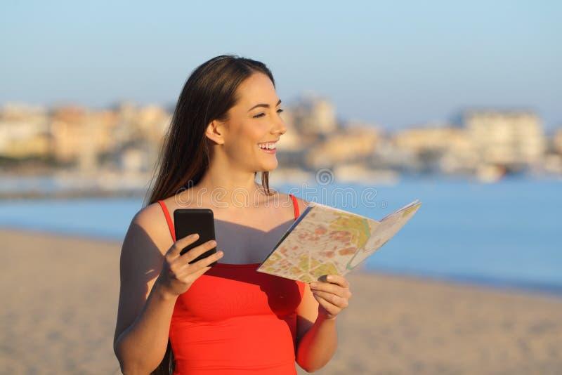 Lycklig turist- hållande översikt och telefon som beskådar stranden royaltyfria foton