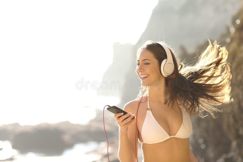 Lycklig turist i bikini som lyssnar till musik på semester arkivbild