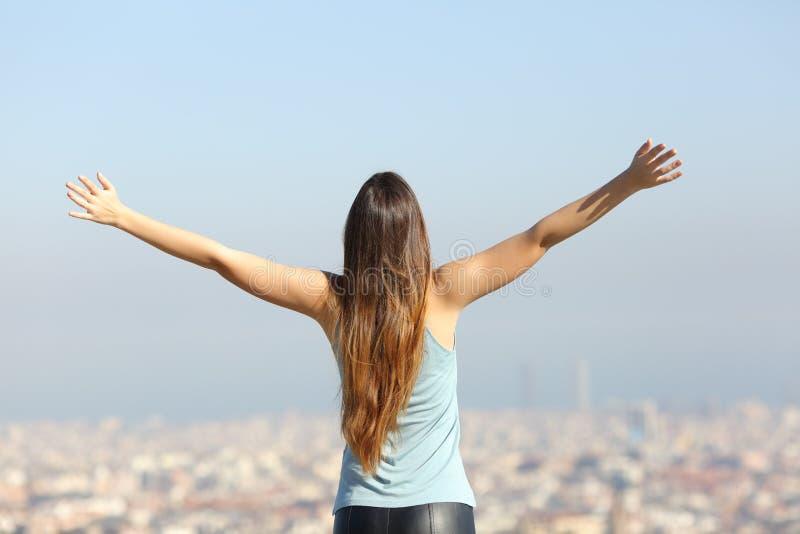 Lycklig turist- kvinna som lyfter armar som ser staden royaltyfria bilder