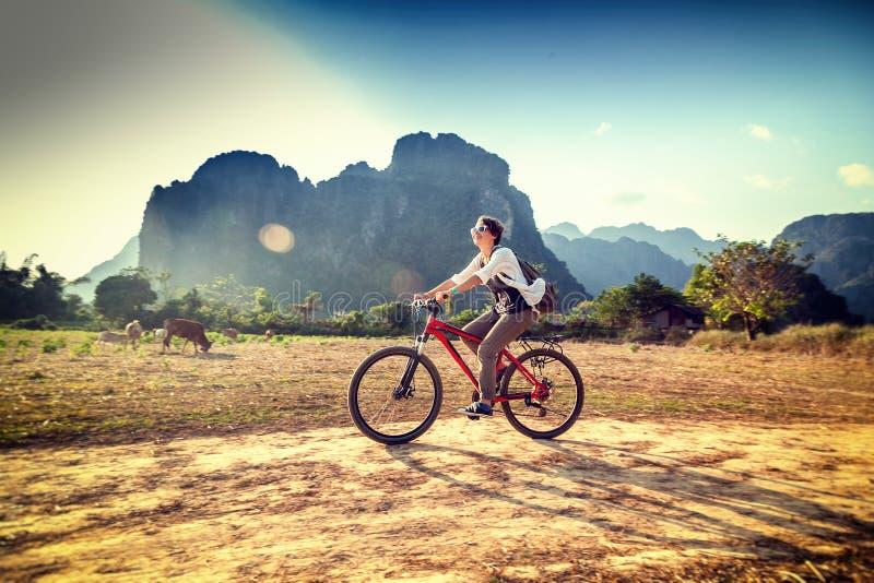 Lycklig turist- kvinna som rider en cykel i bergområde i Laos T arkivbilder