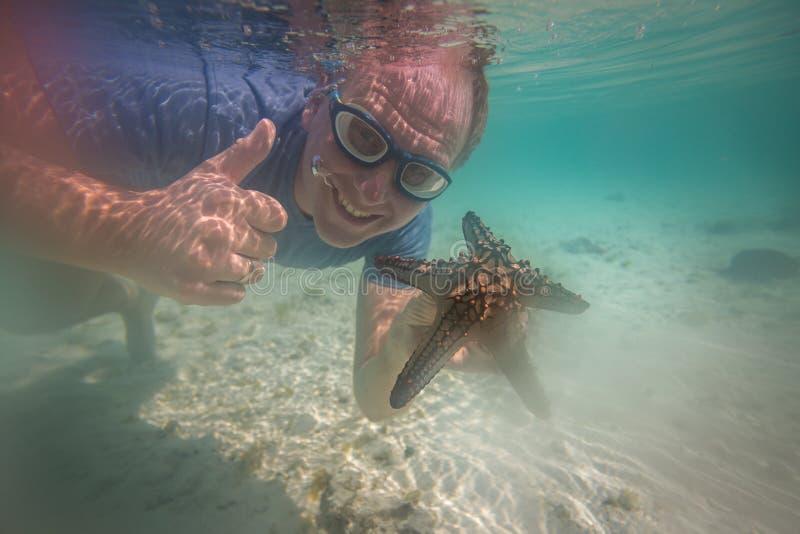 Lycklig turist med sjöstjärnan som tycker om havet royaltyfri foto