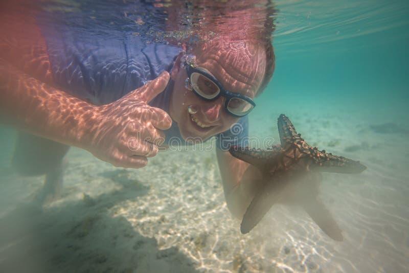 Lycklig turist med sjöstjärnan som tycker om havet royaltyfria foton