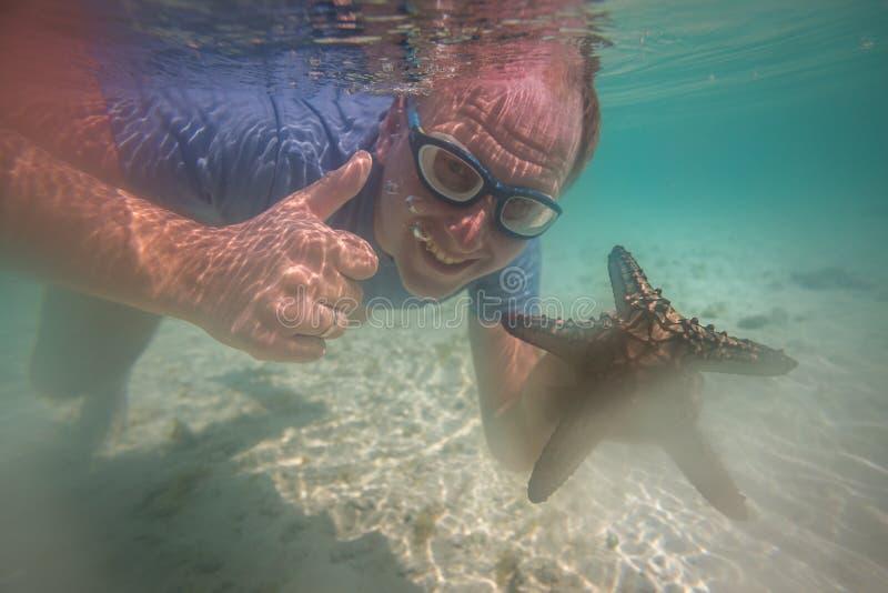 Lycklig turist med sjöstjärnan som tycker om havet royaltyfri fotografi