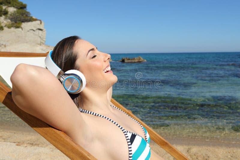 Lycklig turist som lyssnar till musik som kopplar av på stranden royaltyfri foto