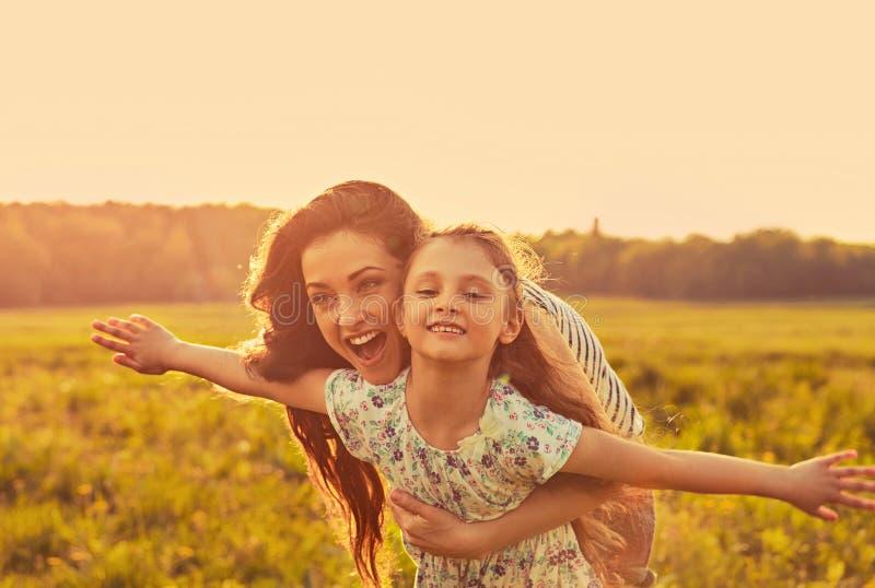 Lycklig tyckande om moder som kramar hennes sk?mtsamma skratta ungeflicka p? ljus sommarbakgrund f?r solnedg?ng closeup royaltyfri foto