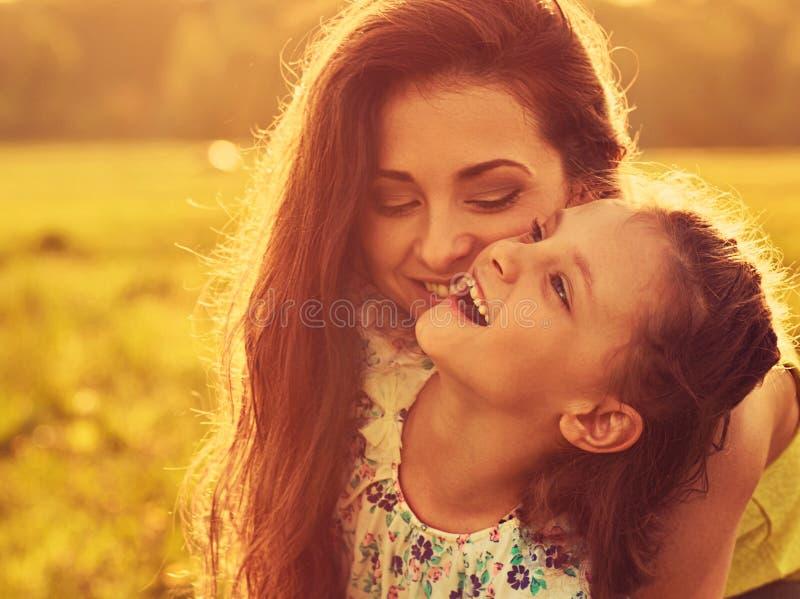 Lycklig tyckande om moder som kramar hennes sk?mtsamma skratta ungeflicka p? ljus sommarbakgrund f?r solnedg?ng closeup arkivfoton