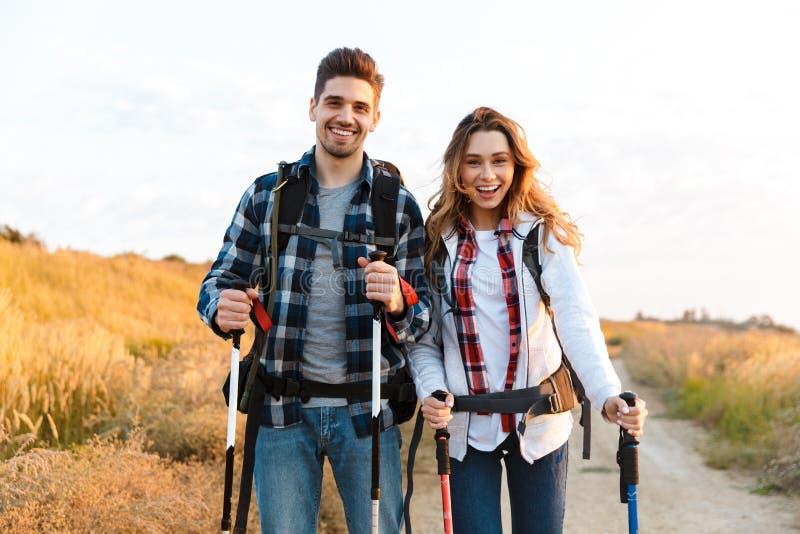 Lycklig ung älska paryttersida med ryggsäcken i fritt alternativt campa för semester fotografering för bildbyråer