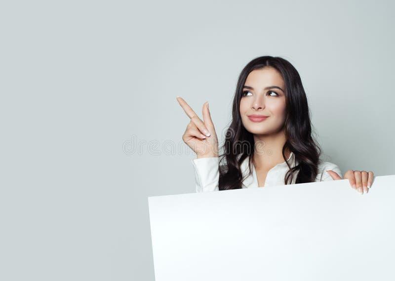 Lycklig ung affärskvinna som pekar upp och visar skylten royaltyfri bild