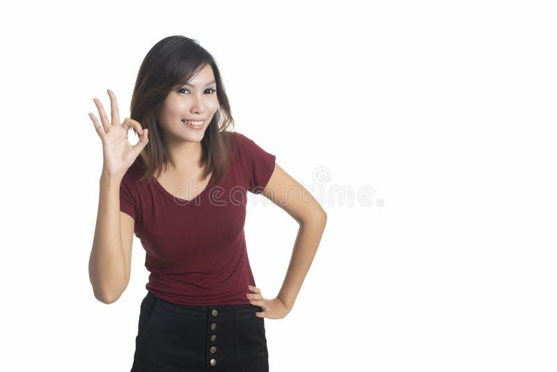 Lycklig ung affärskvinna som visar det ok tecknet som isoleras på vita lodisar royaltyfri foto