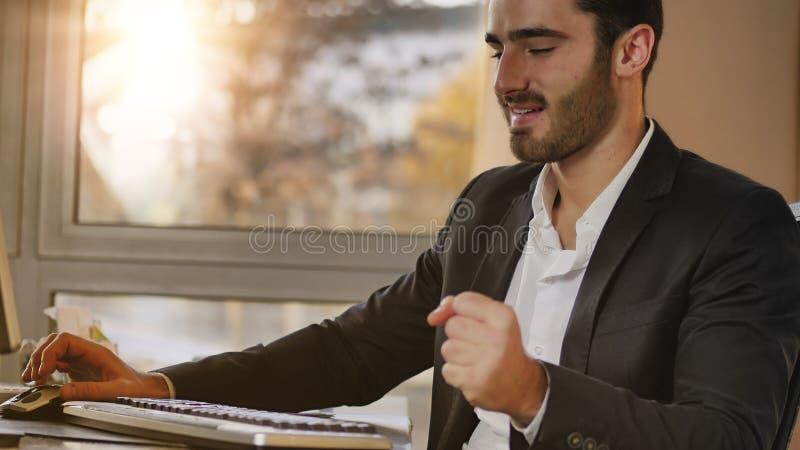 Lycklig ung affärsman i regeringsställning och att sitta på skrivbordet arkivbilder