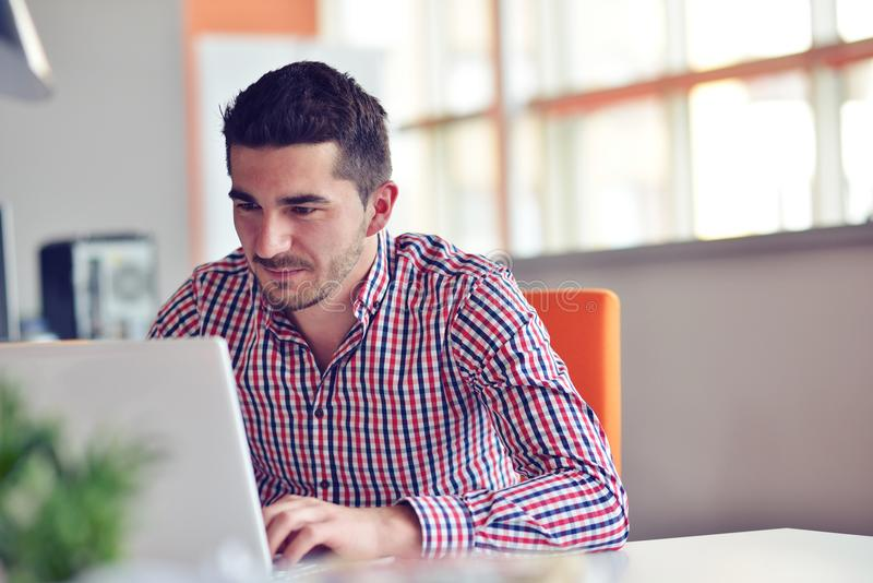 Lycklig ung affärsman som använder bärbara datorn på hans kontorsskrivbord royaltyfri foto