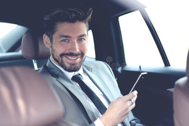 Lycklig ung affärsman som använder mobiltelefonen i baksäte av bilen royaltyfri foto