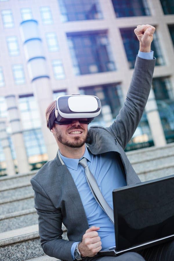 Lycklig ung affärsman som använder VR-skyddsglasögon som framme sitter av en kontorsbyggnad Fira framgång med nävehöjdpunkt i luf royaltyfria bilder