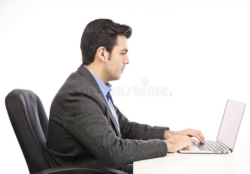 Lycklig ung affärsman som arbetar på bärbara datorn arkivfoto