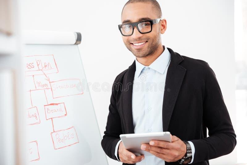 Lycklig ung affärsman som i regeringsställning använder PCminnestavlan arkivbilder
