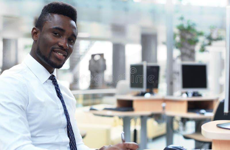 Lycklig ung afrikansk amerikanaffärsman som i regeringsställning ser kameran på arbetsplatsen royaltyfri foto