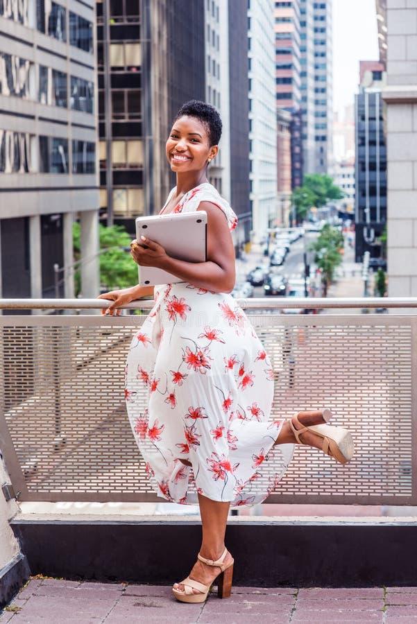 Lycklig ung afrikansk amerikanhögskolestudent som studerar i nya Yor royaltyfria foton