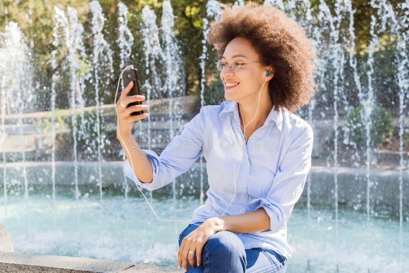 Lycklig ung afrikansk amerikankvinna i tillfälliga kläder, genom att använda Smartphones för socialt nätverk arkivfoton