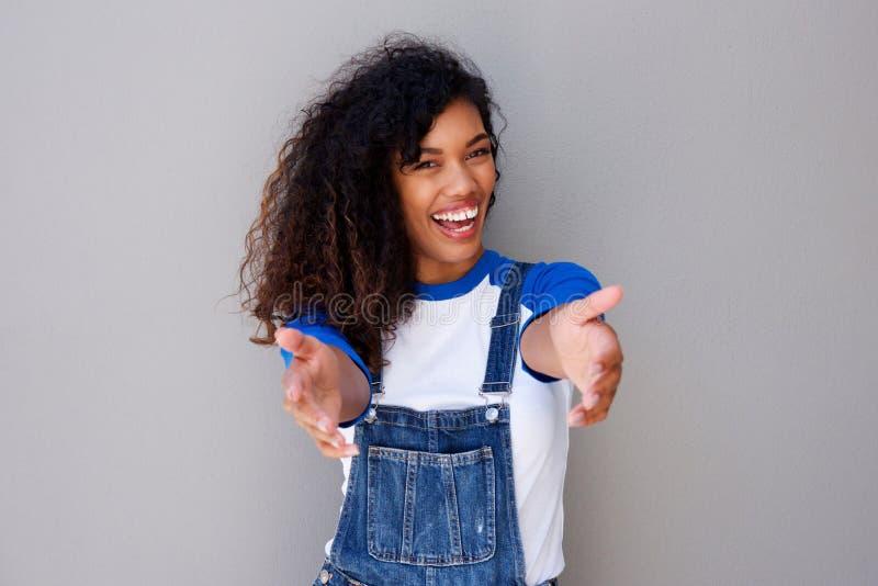Lycklig ung afrikansk amerikankvinna som välkomnar med öppna armar arkivbild