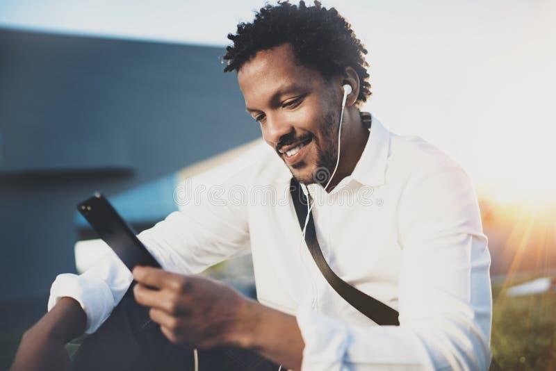 Lycklig ung afrikansk amerikanman i headphone som går på den soliga staden och tycker om för att lyssna till musik på hans elektr arkivfoton
