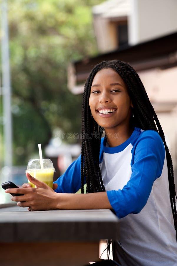 Lycklig ung afrikansk kvinna med mobiltelefonen på det utomhus- kafét royaltyfri fotografi