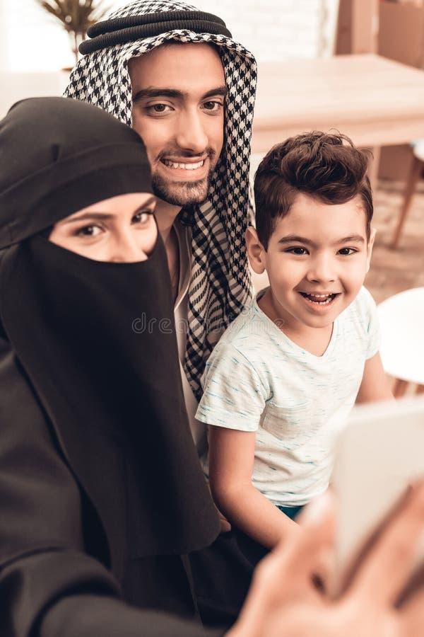 Lycklig ung arabisk familj som hemma tar Selfie royaltyfri foto