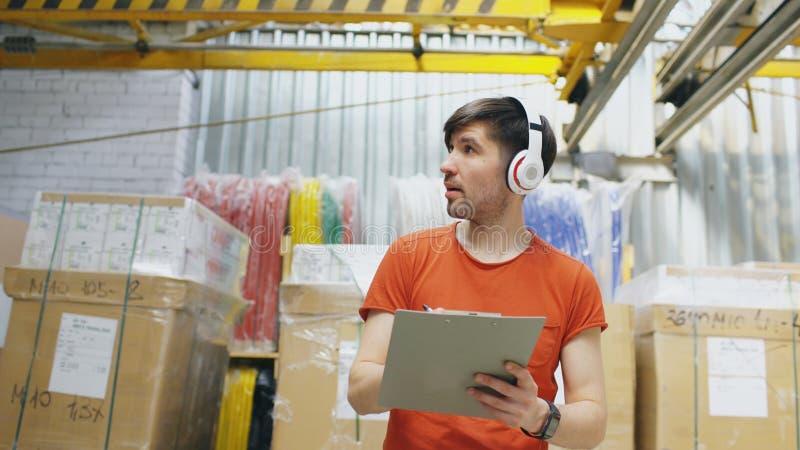 Lycklig ung arbetare i industriellt lager som lyssnar till musik under arbete Mannen i hörlurar har gyckel på arbetsplatsen arkivfoto