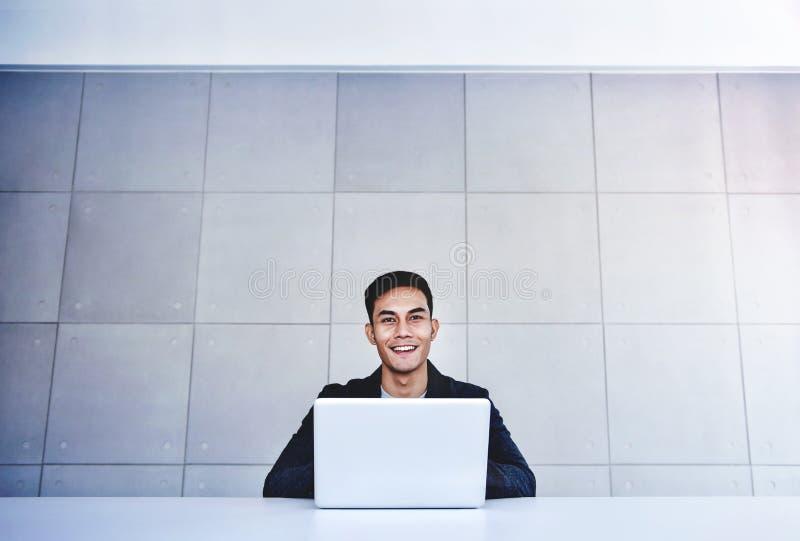 Lycklig ung asiatisk affärsman Working på datorbärbara datorn i hans arbetsplats Le och se kameran royaltyfria bilder