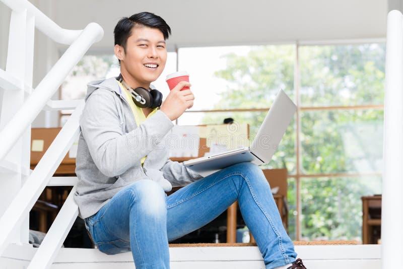 Lycklig ung asiatisk anställd som använder en bärbar dator i ett modernt kontor royaltyfria foton