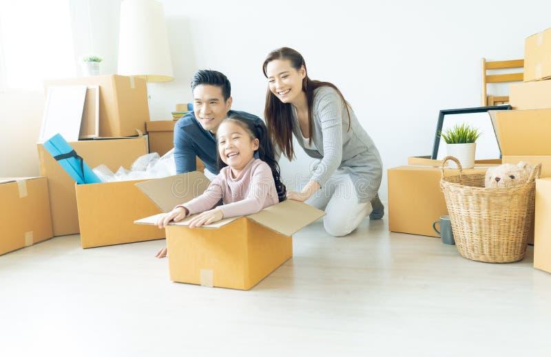 Lycklig ung asiatisk familj av tre som har gyckel som flyttar sig med cardboa royaltyfria bilder