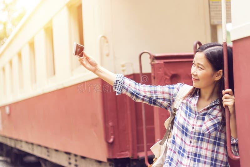 Lycklig ung asiatisk handelsresandekvinna som tar selfiefotoet från mobiltelefonen på drevstationen, medan resa royaltyfri foto