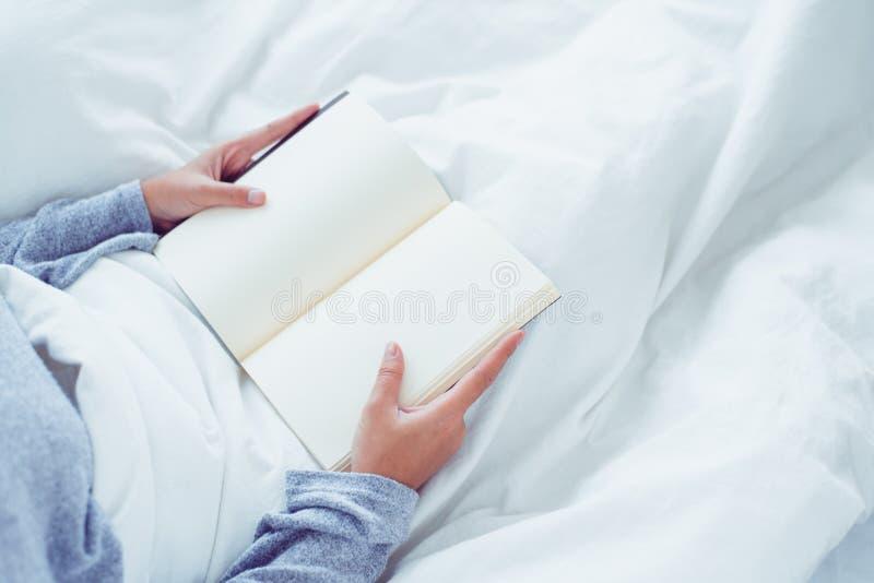 Lycklig ung asiatisk kvinna för livsstil som tycker om att ligga på sängläseboknöjet i tillfälliga kläder hemma fotografering för bildbyråer
