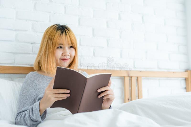 Lycklig ung asiatisk kvinna för livsstil som tycker om att ligga på sängläseboknöjet i tillfälliga kläder hemma arkivbilder